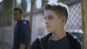 Tonårs- pojkar som lutar på metall, fäktar, den barnsliga interneringsanstalten, barnhem lager videofilmer