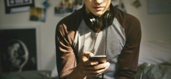 Tonårs- pojke i ett sovrum som lyssnar till musik till och med hans smartphone arkivbilder