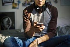 Tonårs- pojke i ett sovrum som lyssnar till musik till och med hans smartphone arkivfoton