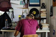 Tonårs- pojke i ett sovrum som ut gör stressat för arbete och frustrerat arkivfoton