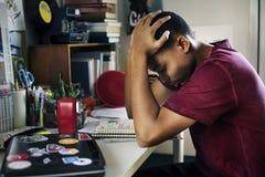 Tonårs- pojke i ett sovrum som ut gör stressat för arbete och frustrerat arkivbild