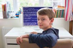 Tonårs- pojke i kod för sovrumhandstildator royaltyfria foton