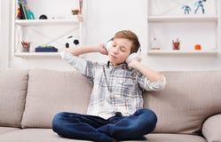 Tonårs- pojke i tillfällig tyckande om musik i hörlurar hemma royaltyfria bilder