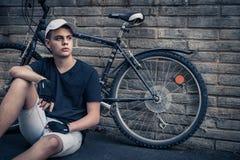 Tonårs- pojke med cykeln som är främst av en tegelstenvägg Arkivbilder