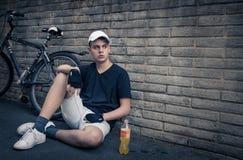 Tonårs- pojke med cykeln som är främst av en tegelstenvägg Royaltyfri Fotografi