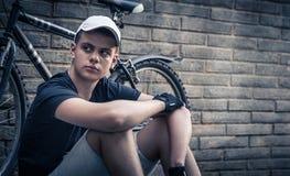 Tonårs- pojke med cykeln som är främst av en tegelstenvägg arkivfoto