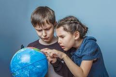 Tonårs- pojke med en flicka som ser en jordklotvisning Royaltyfri Foto