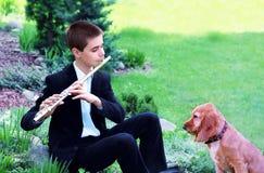 Tonårs- pojke med flöjten och hunden