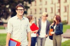 Tonårs- pojke med klasskompisar på baksidan arkivfoto