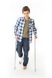 Tonårs- pojke med kryckor och en förbinda på hans högra ben Royaltyfri Foto