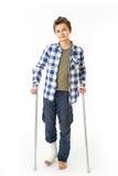 Tonårs- pojke med kryckor och en förbinda på hans högra ben Arkivfoto