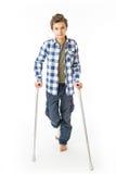 Tonårs- pojke med kryckor och en förbinda på hans högra ben Arkivbild