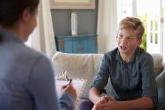 Tonårs- pojke med problem som talar med den hemmastadda lägerledaren arkivfoto