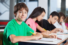 Tonårs- pojke med vänner som studerar på skrivbordet Arkivfoton
