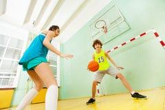 Tonårs- pojke och flicka som spelar basket i idrottshall Royaltyfri Fotografi