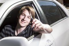 Tonårs- pojke och ny chaufför bak hjulet av hans bil Royaltyfri Fotografi