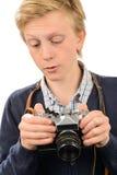 Tonårs- pojke som använder den retro kameran Arkivfoton