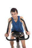 Tonårs- pojke som använder en motionscykelkondition royaltyfri bild