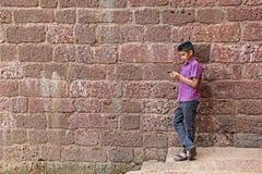 Tonårs- pojke som arbetar på Smartphone Arkivbilder