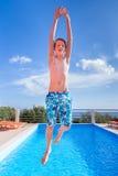 Tonårs- pojke som högt hoppar ovanför blå simbassäng Arkivbilder