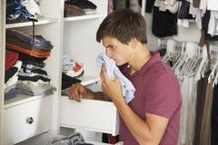 Tonårs- pojke som kontrollerar friskhet av kläder i garderob Arkivbild