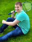 Tonårs- pojke som ler, medan rymma en tennisracket Fotografering för Bildbyråer