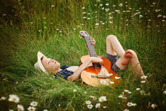 Tonårs- pojke som ligger på gräs med hans akustiska gitarr Arkivbilder