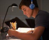 Tonårs- pojke som lyssnar till musikstunden som studerar på skrivbordet i sovrum i afton Arkivbilder