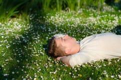 Tonårs- pojke som mycket ligger på ängen av vita blommor i sommar Royaltyfri Foto