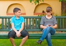 Tonårs- pojke som ser med förälskelse på den likgiltiga flickan Arkivfoto