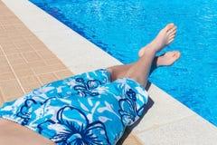 Tonårs- pojke som solbadar på simbassängen royaltyfri fotografi