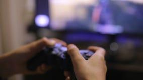 Tonårs- pojke som spelar en datorvideospel med en styrspak arkivfilmer