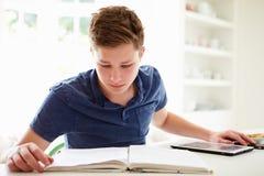 Tonårs- pojke som studerar genom att använda den Digital minnestavlan hemma Arkivbild