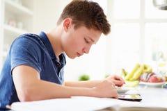 Tonårs- pojke som studerar genom att använda den Digital minnestavlan hemma Royaltyfri Bild