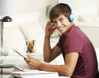 Tonårs- pojke som studerar på skrivbordet i sovrum genom att använda den Digital minnestavlan Fotografering för Bildbyråer