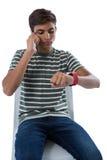 Tonårs- pojke som talar på smartphonen som ser hans smartwatch Arkivfoto