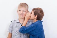 Tonårs- pojke som viskar i örat en hemlighet till Royaltyfri Foto