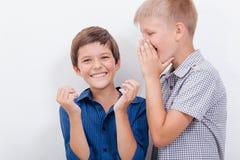 Tonårs- pojke som viskar i örat en hemlighet till Royaltyfria Foton
