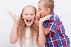 Tonårs- pojke som viskar i örat en hemlighet till tonårigt Royaltyfri Foto