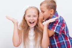 Tonårs- pojke som viskar i örat en hemlighet till tonårigt Fotografering för Bildbyråer