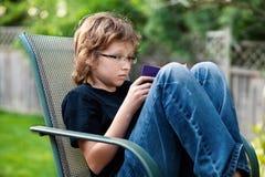 Tonårs- pojke utanför läsning på en stol Royaltyfria Foton