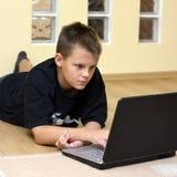 tonårs- pojkegolvbärbar dator Royaltyfria Foton