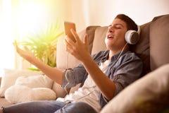 Tonårs- sjunga från hennes mobiltelefonsammanträde på soffan hemma royaltyfri fotografi