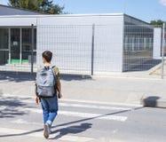 Tonårs- skolapojke med en ryggsäck på hans baksida som går till skolan Arkivfoto