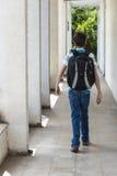 Tonårs- skolapojke med en ryggsäck på hans baksida som går till skolan Arkivbilder