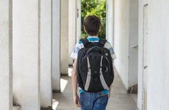 Tonårs- skolapojke med en ryggsäck på hans baksida som går till skolan Royaltyfri Foto