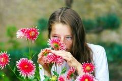 Tonårs- skolflickastående med naturliga blommor Arkivbild