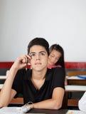 Tonårs- skolpojke som ser bort, medan sitta på Royaltyfria Bilder