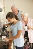 Tonårs- sondotter som delar kopp te med farmodern i kök Arkivfoton