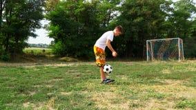 Tonårs- sparkar en fotbollboll lager videofilmer